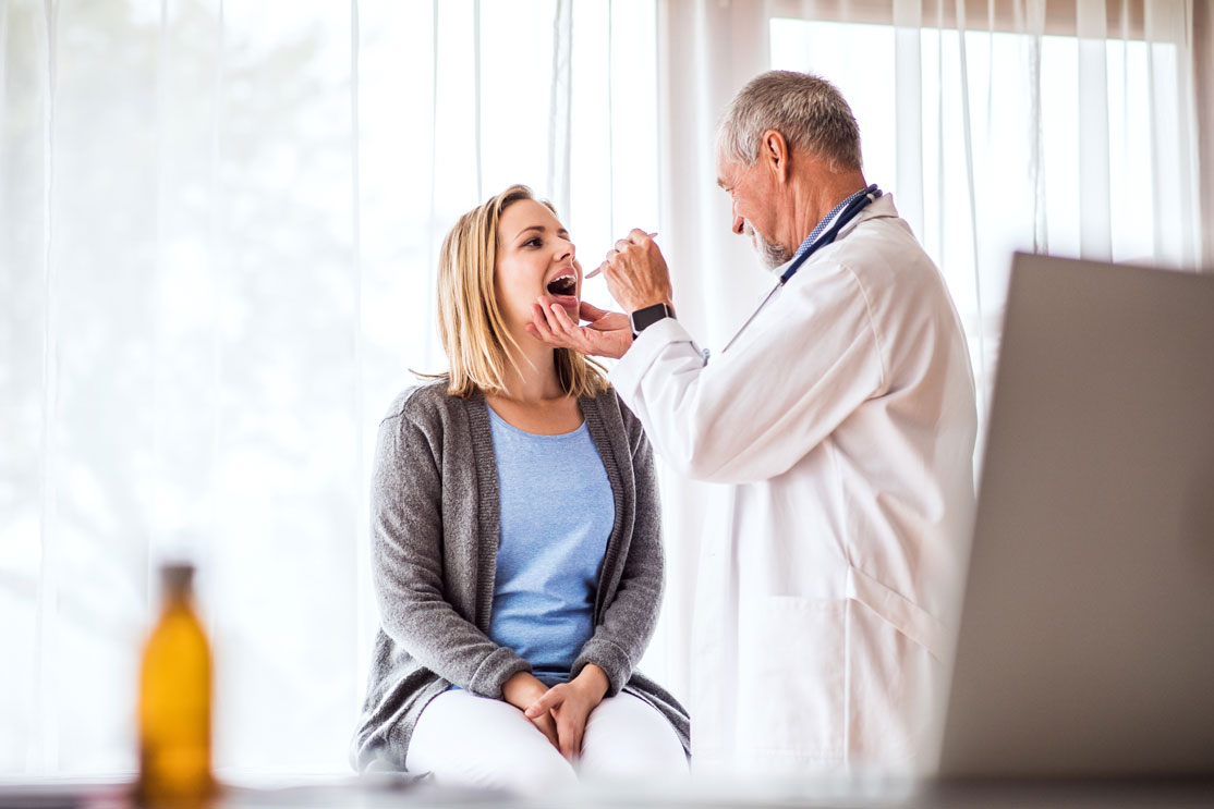doctor examining a young woman's throat